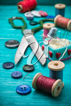 thread buttons for crafts on turquoise wooden background.Selective focus