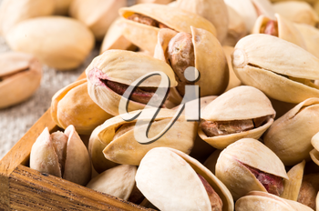 Macro close-up view of a group of salted pistachios in a small wooden box with a shallow depth of field