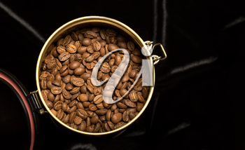 Coffee beans in a jar on a velvet fabric, warm shade, studio shot