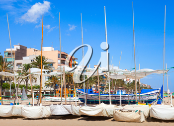 Sailing boats lay on the sandy beach in Calafell town, coast of Mediterranean sea, Catalonia, Spain