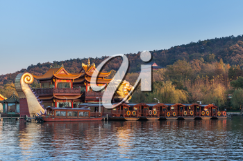 Hangzhou, China - December 5, 2014: Traditional Chinese wooden pleasure boats and Dragon ship stand on the West Lake. Famous park in Hangzhou city center, China