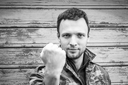 Young Caucasian man in camouflage showing his big fist. Monochrome outdoor portrait over rural wooden wall