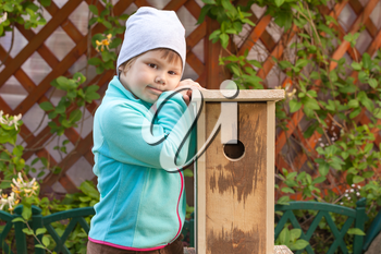 Cute smiling Caucasian blond girl stands near new handmade nesting box