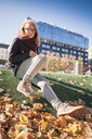Beautiful Caucasian blond teenage girl in glasses sitting in autumnal city park with falling leaves