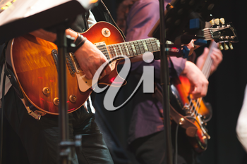 Rock and roll music background, guitar players on a stage with colorful illumination, selective focus