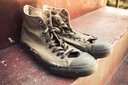 Pair of old sneakers standing on red concrete stairs, closeup photo with selective focus