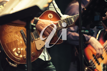 Rock and roll music background, guitar players on a stage, selective focus and  retro tonal correction filter, old instagram style