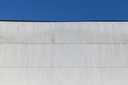 Industrial building wall made of corrugated metal sheet, under blue sky