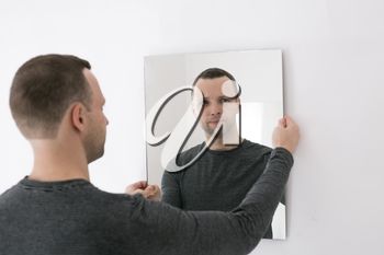 Studio portrait of young man standing near white wall with mirror