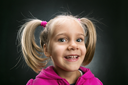 Smiling little girl in rose jacket on grey background