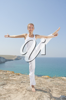 Beautiful woman in white cloth practices Yoga in mountains against the sea