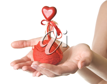 Hands with red ball of threads and heart