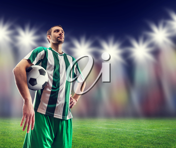 Football-player holding a ball against light