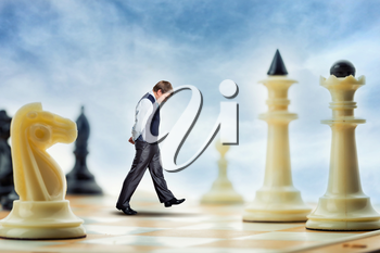 Businessman is walking on the chess board thinking