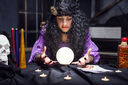 Sorceress looking at crystal ball in her room