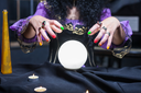 Close up of sorceress working with crystal ball in her room