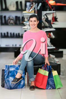 Woman sitting with many shopping bags in the shoe store