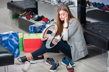 Young woman sitting on the floor in the shoe store thinks over what shoes to choose