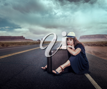 Young girl with luggage traveling hitchhiking. Rocky mountains on the background. Travel concept in retro style.