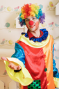 Happy clown with red nose and colourful costume offers friendship.
