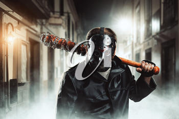 Spooky serial maniac in hockey mask holding bloody baseball-bat and waiting for his victim on night city street.