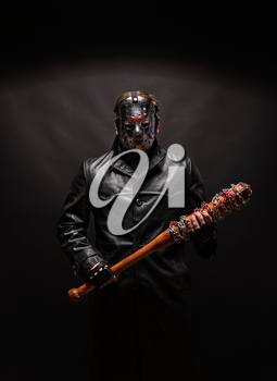 Bloody maniac in hockey mask and black leather coat with bat on black background.
