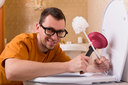 Man in glasses cleaning the toilet bowl. Luxury bathroom interior on background