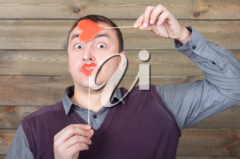 Young man with funny red lips and heart on a sticks in hand, wooden background. Fun photo props and accessories for shoots