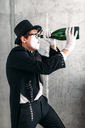 Pantomime theater actor performing with big bottle. Comedy mime artist in suit, gloves, glasses, make-up mask and hat