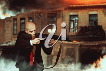 Killer in suit and red tie shoot a machine gun, night urban landscape with destroyed buildings on background. Contract murderer wallpaper or poster concept