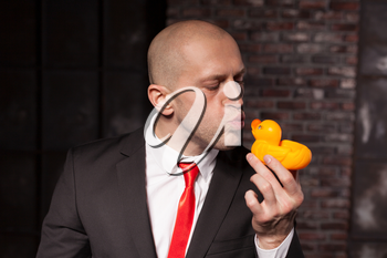 Special agent kissing little toy duck. Contract killer in suit and red tie shows his fears and secrets. Hired murderer wallpaper or background concept