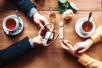 Female and male hands with wedding ring top view, wooden table, rose and cups on background. Couple romantic date. Marriage proposal