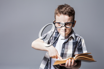 Strict boy in glasses with book in hands, studio photo shoot. School education concept