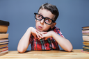 Little schoolboy learns homework at the desk in classroom. Pupil in glasses gets knowledge
