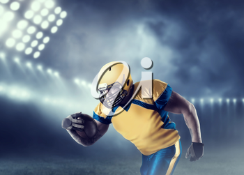 American football player with ball in hands, on sport arena. National league