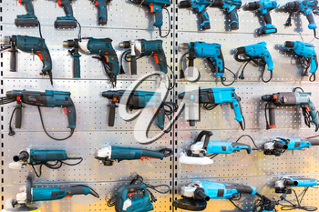 Hand-held power tools on stand in store. Hammer drills, grinding machines, electrical screwdrivers, workshop tools