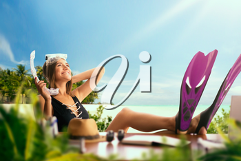 Cute woman in a swimsuit and in flippers at the table, palms, ocean and paradise island on background. Dreams about a vacation concept, daydreaming