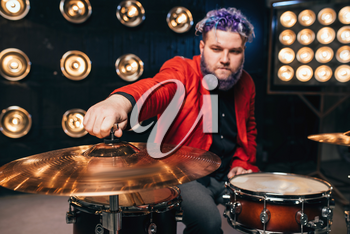 Bearded drummer in red suit on the stage with lights, retro style. Musical performer with colorful hair, drum instrument