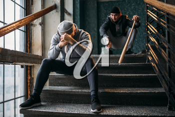 Two male gangsters are sitting on the stairs. Street robbers with baseball bat and knife waiting for victim. Crime concept