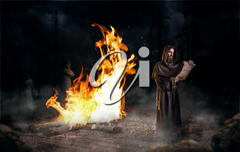 Medieval monk reads a prayer in the ancient manuscript against a big fire, religion. Mysterious friar in dark cape. Mystery and spirituality