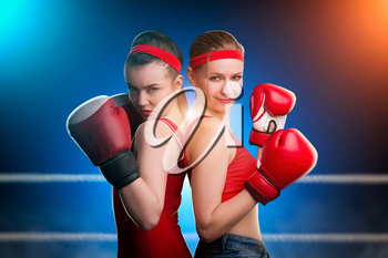 Two female boxers in red boxing gloves standing back to back. Fighting sport and martial art concept