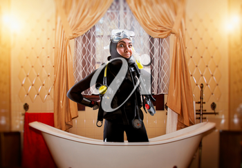 Female diver in wetsuit and diving gear is in the bath, bathroom interior on background. Underwater sport