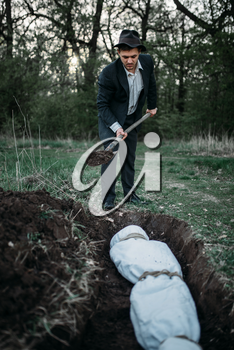 Maniac with a shovel buries victim into a grave, the body wrapped in a canvas, serial murderer concept