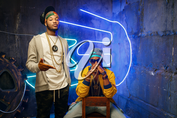 Two black rappers, neon lights on background. Rap performers in subway, underground lifestyle