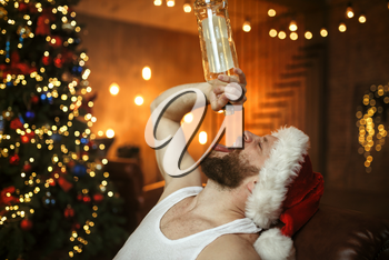 Bad Santa claus drinks alcohol, nasty party. Unhealthy lifestyle, bearded man in holiday costume, new year and alcoholism