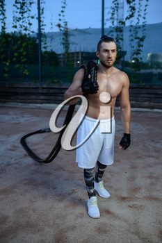 Muscular man poses with crossfit ropes, street workout. Fitness training on sports ground outdoor, male person pumps muscles, active urban lifestyle