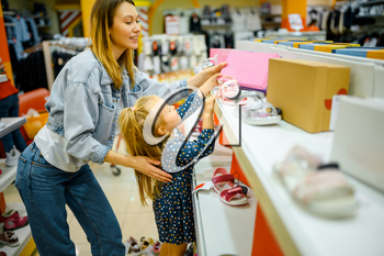 Mother and little baby looking on shoes in kid's store. Mom and adorable girl near the showcase in children's shop, happy childhood, family makes a purchase in market