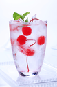 Glass of iced drink with maraschino cherries