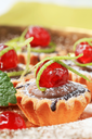 Chocolate filled tartlets topped with glace cherries