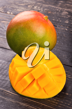 Fresh mango fruit with half cut into pieces on the dark table closeup